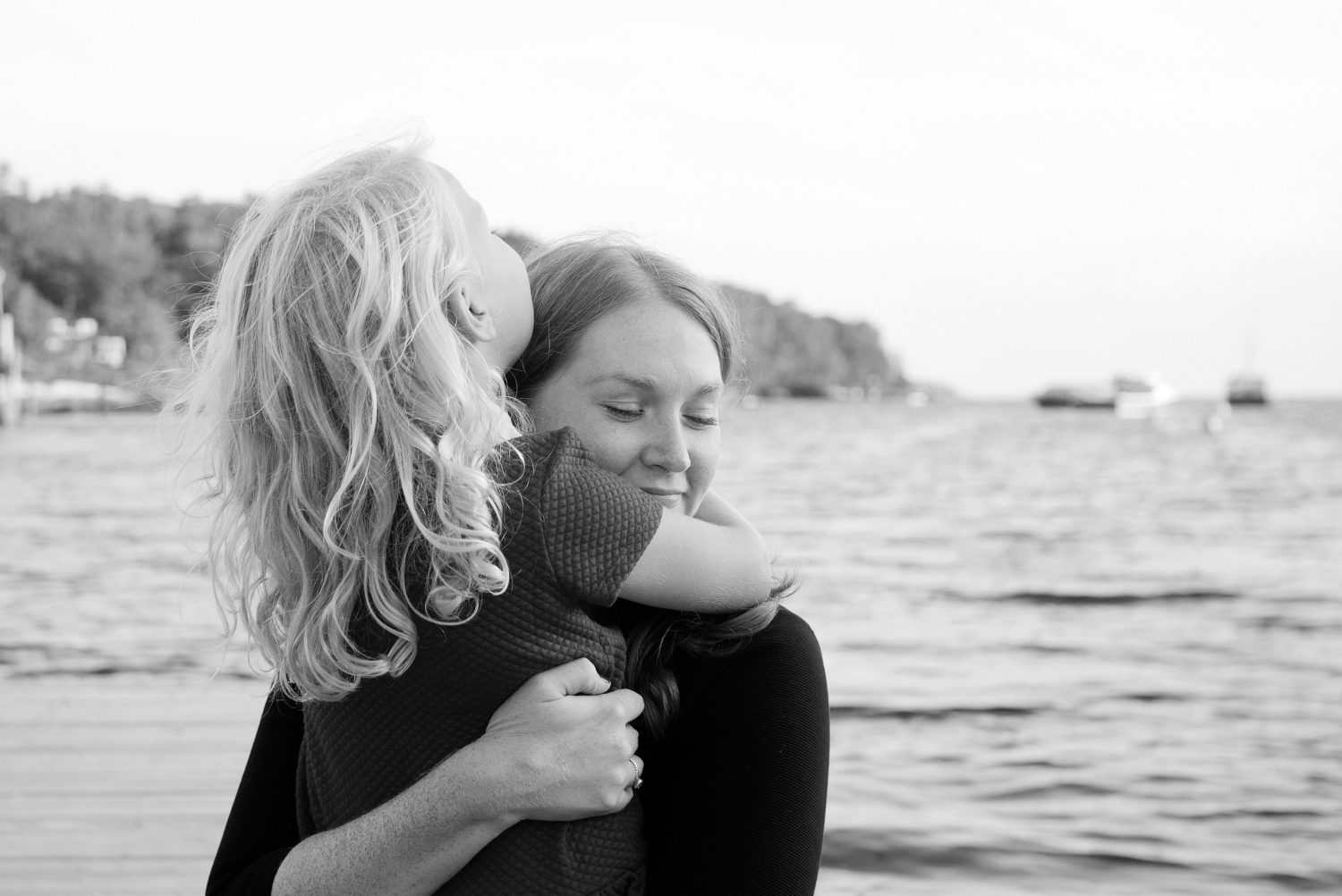 black and white image of young daughter hugging mother