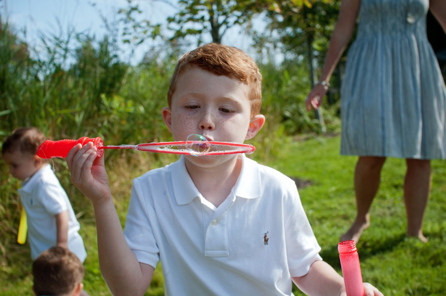 Young red headed boy blowing bubbles