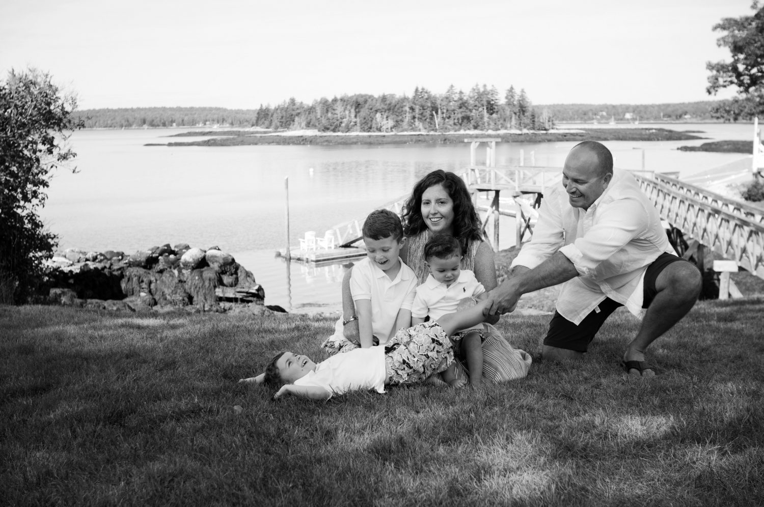 Silly Black and white photo of young family sitting on the grass at the shore