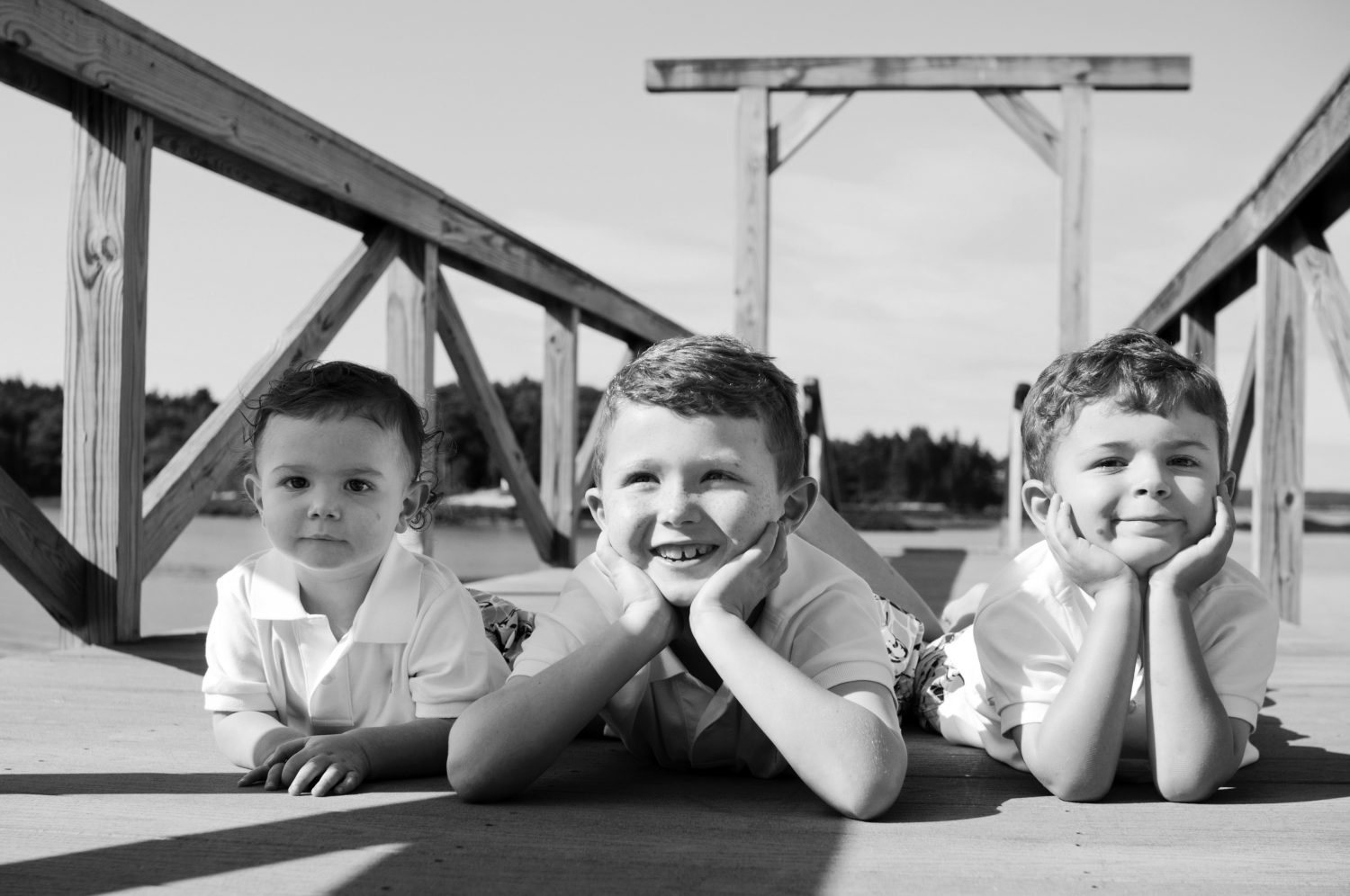 Portrait of three young boys laying on their bellies on a dock at the coast