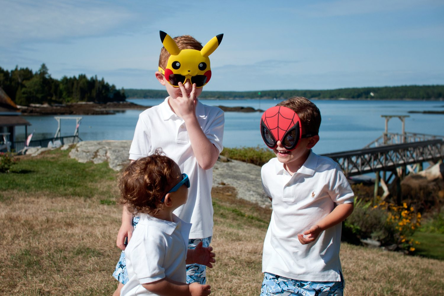 Three young siblings wearing face masks at their beach house