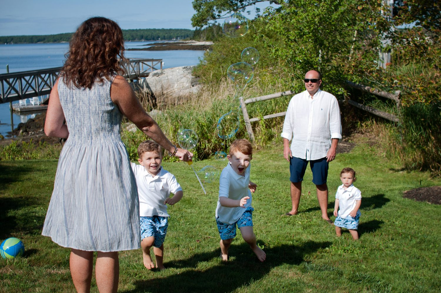 Family of five playing with bubbles in the grass at a coastal vacation home