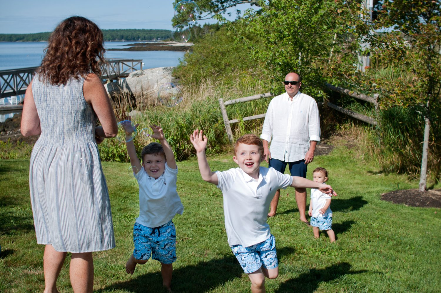 Children chasing bubbles at their coastal rental home