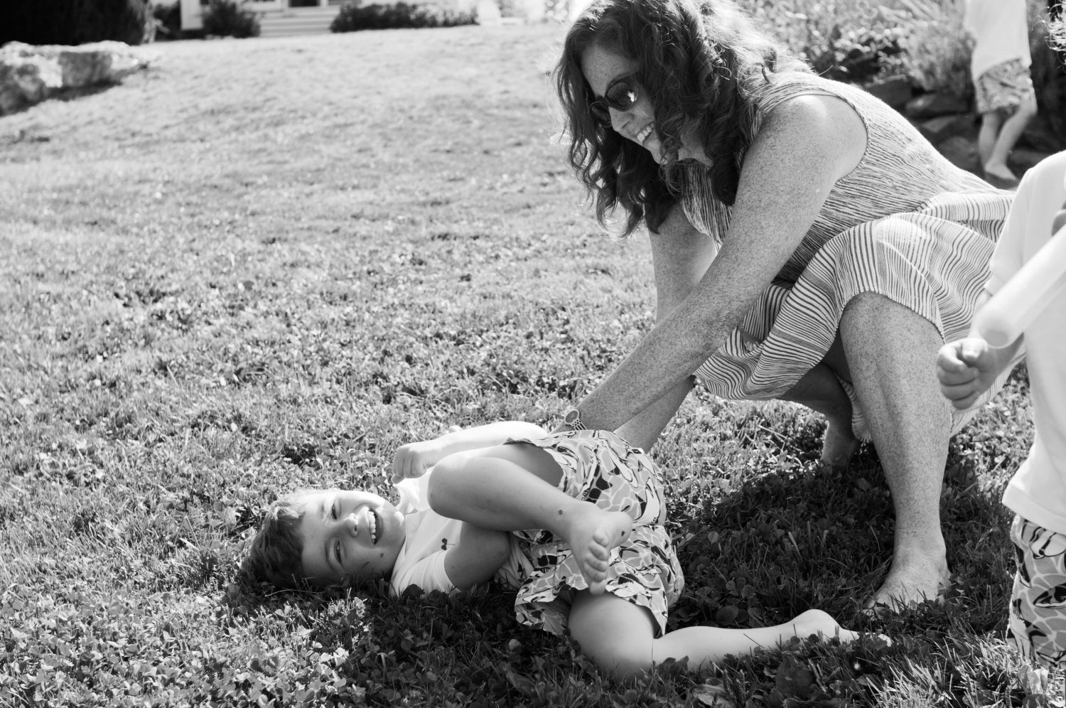 Black and white photo of mother tickling her young son in the grass