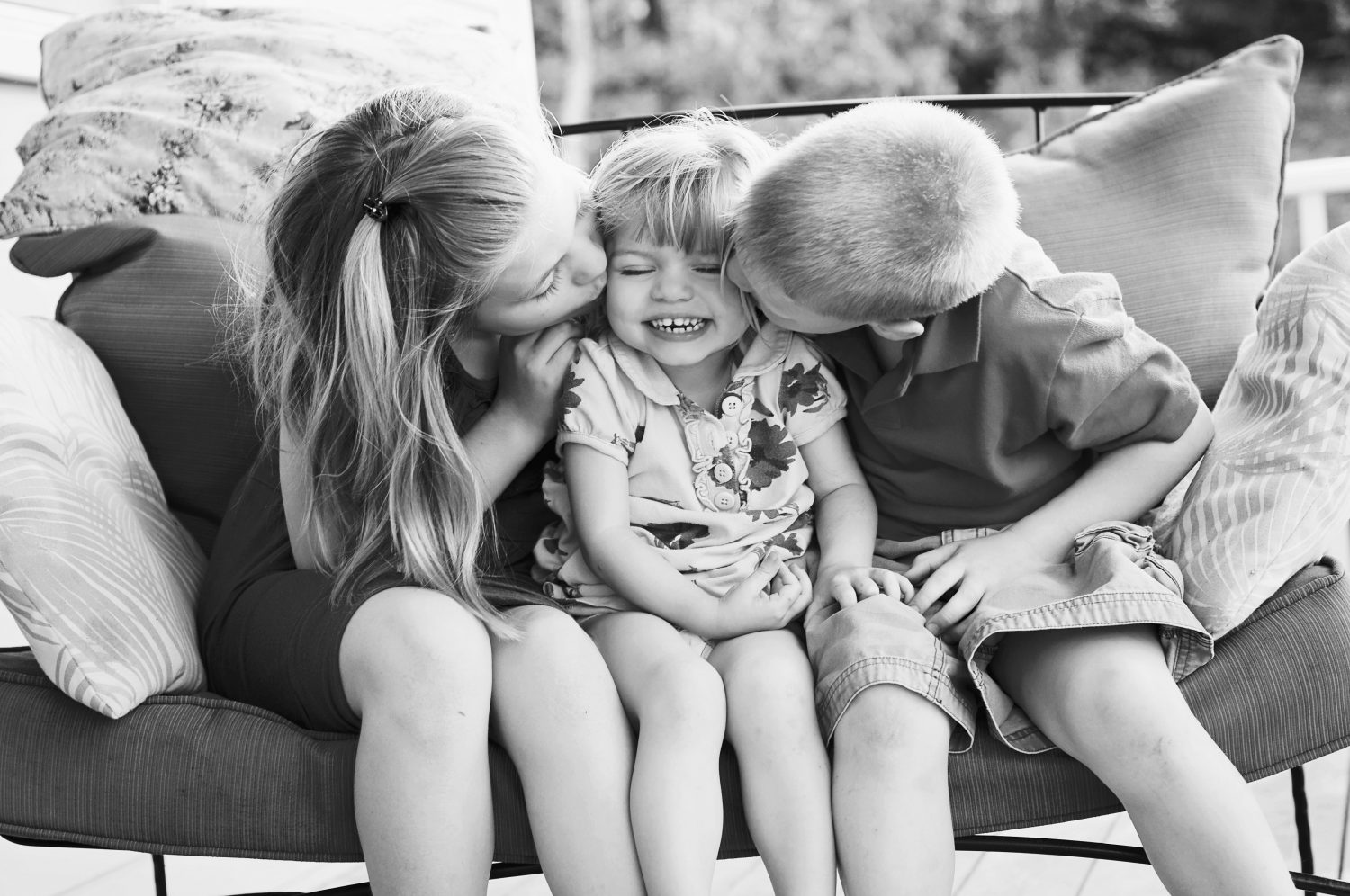 two siblings kissing the cheek of a third sibling while sitting together
