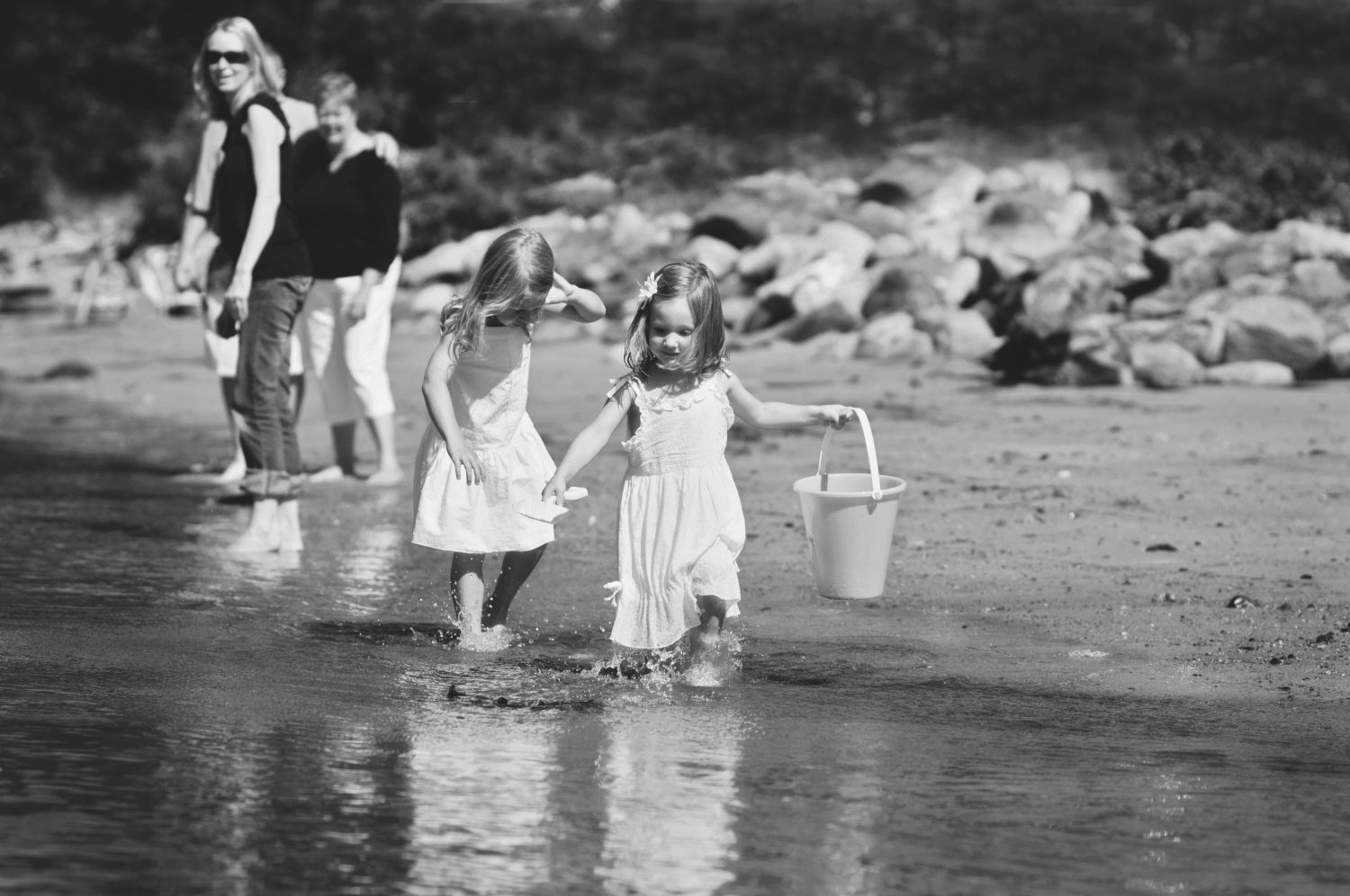 two little girls in white dresses running barefoot along the waters edge holding buckets