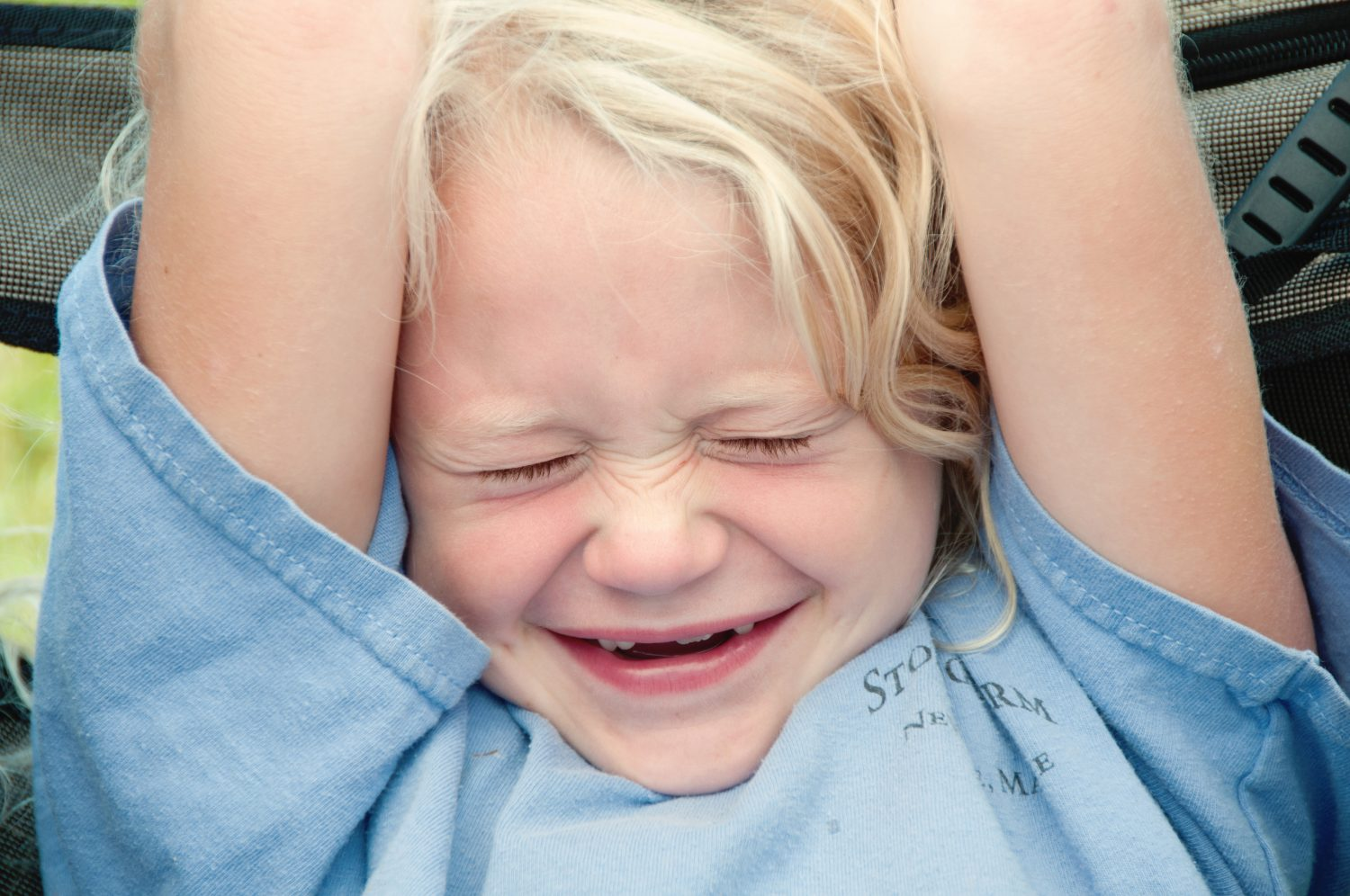 little blonde girl with missing front teeth smiling with eyes closed