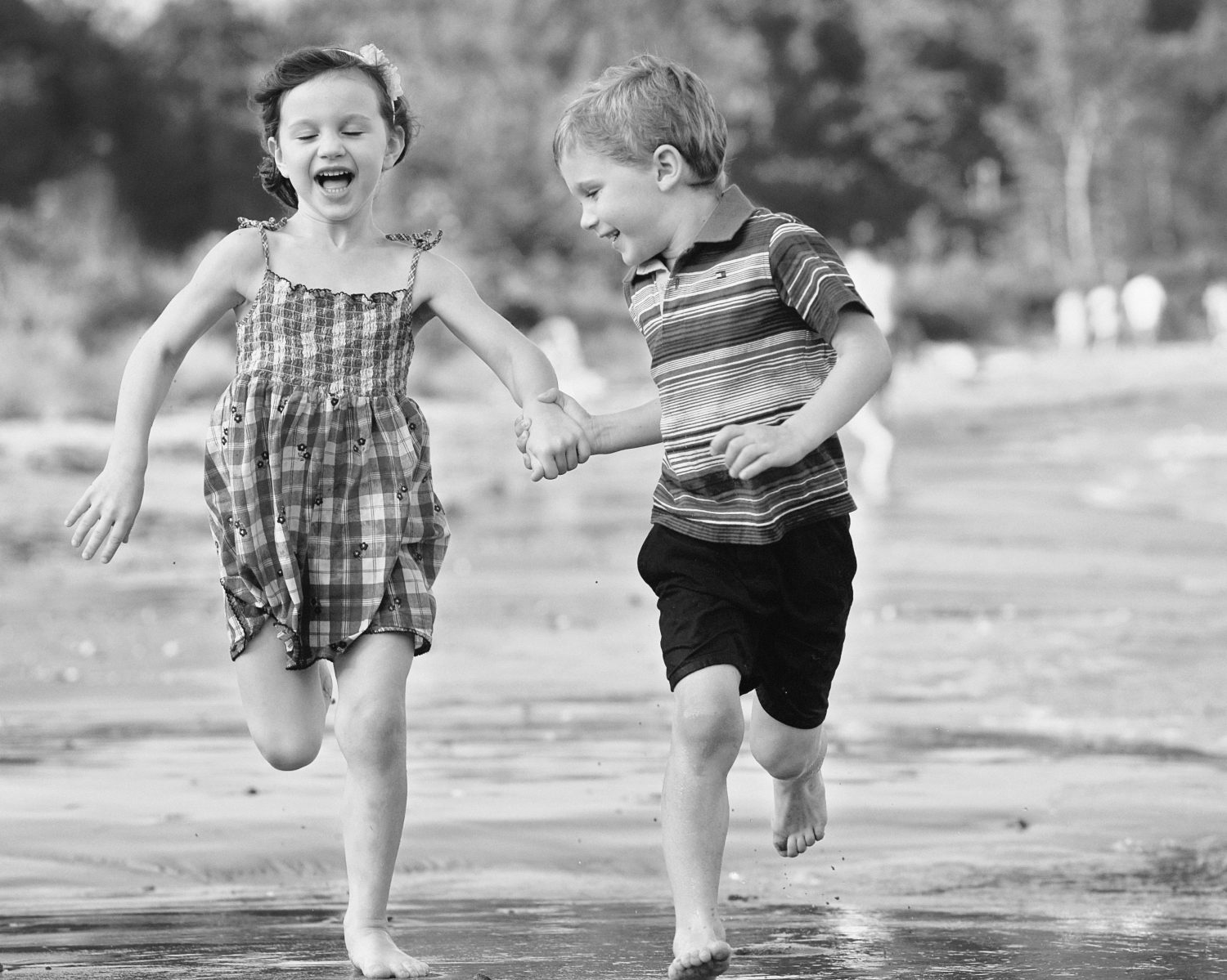 black and white photo of young twin boy and girl holing hands while running along the waters edge