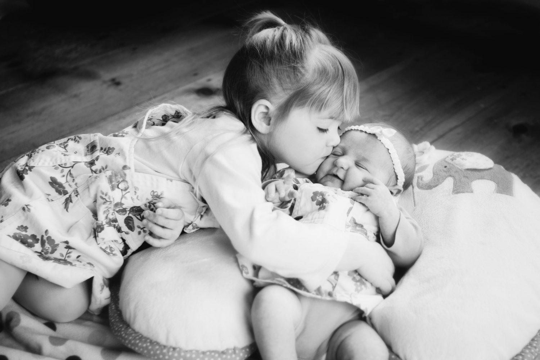 older sister kissing her baby sisters cheek