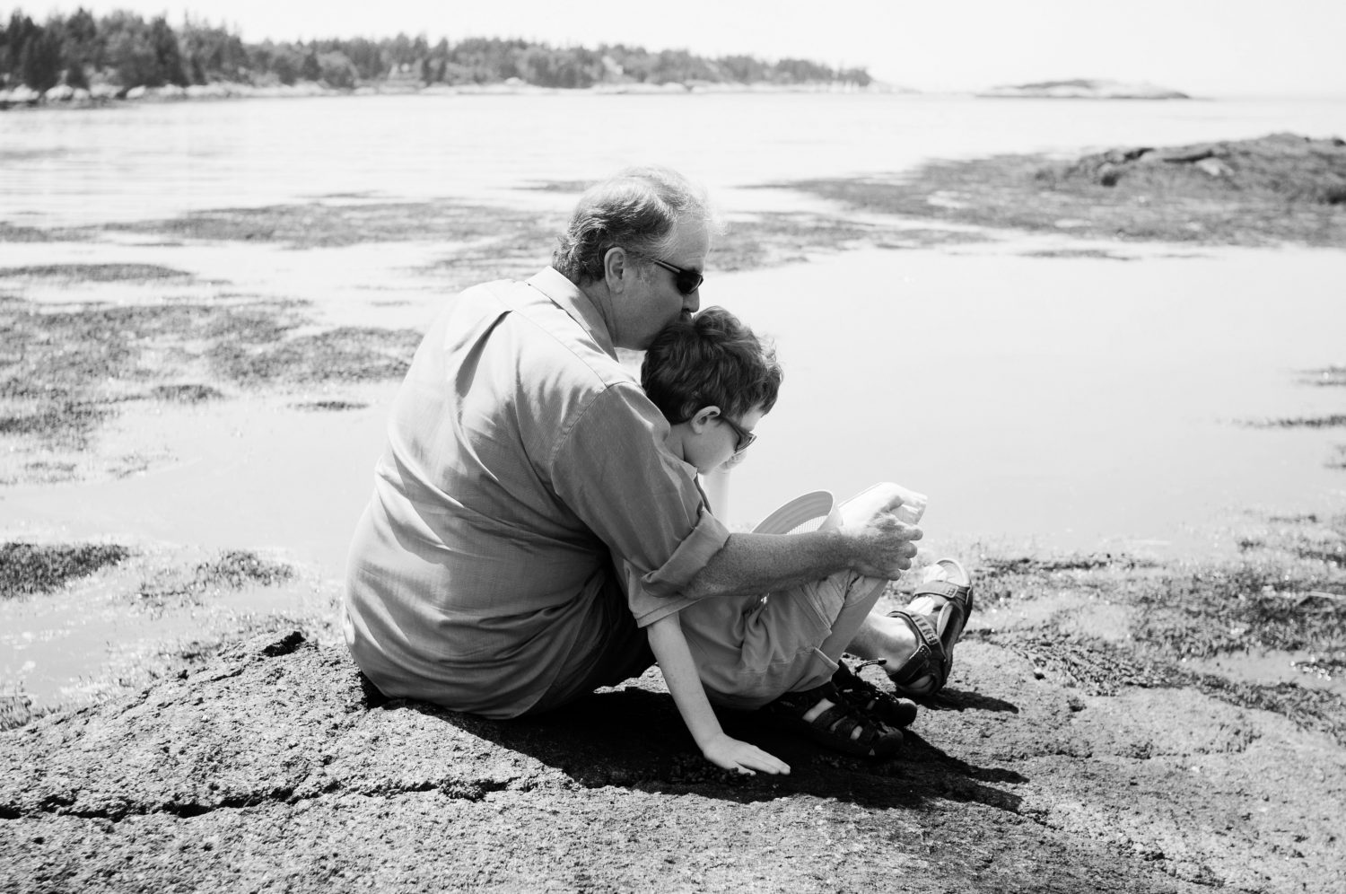 father and son sitting together on the rocky shoreline