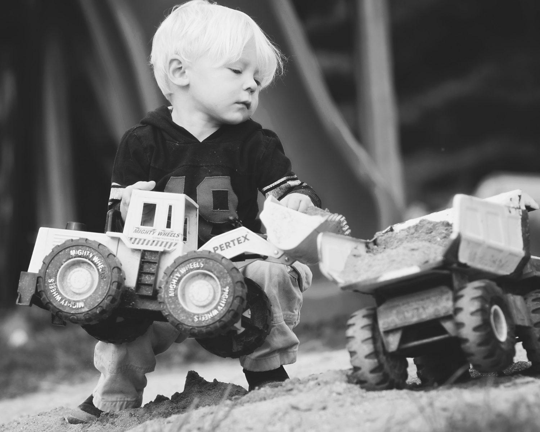 toddler boy playing with big toy trucks in sandbox