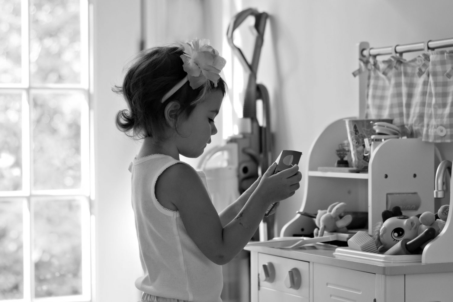 black and white photograph of little girl playing with toy kitchen