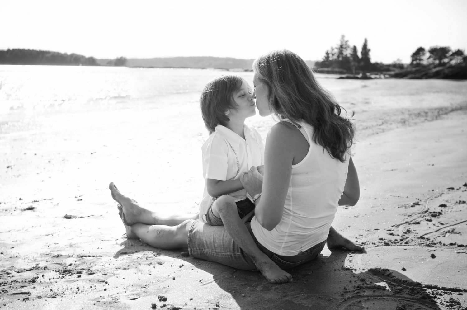 young son sitting on mothers lap facing her while on the beach