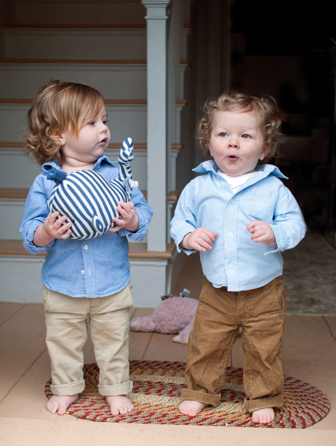 two toddlers standing next to each other smiling