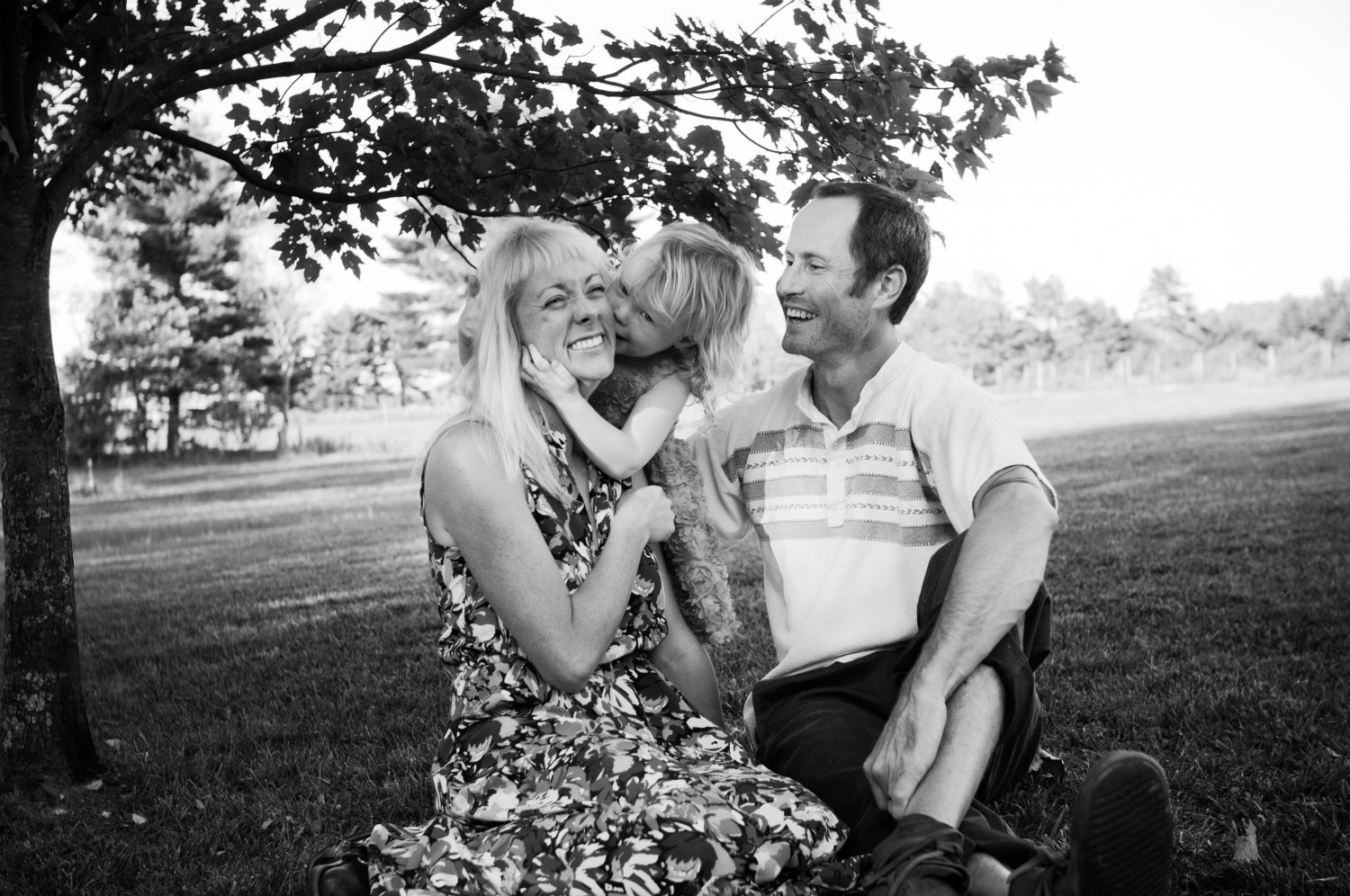 black and white candid portrait of parents with young daughter laughing together on the grass beneath a tree
