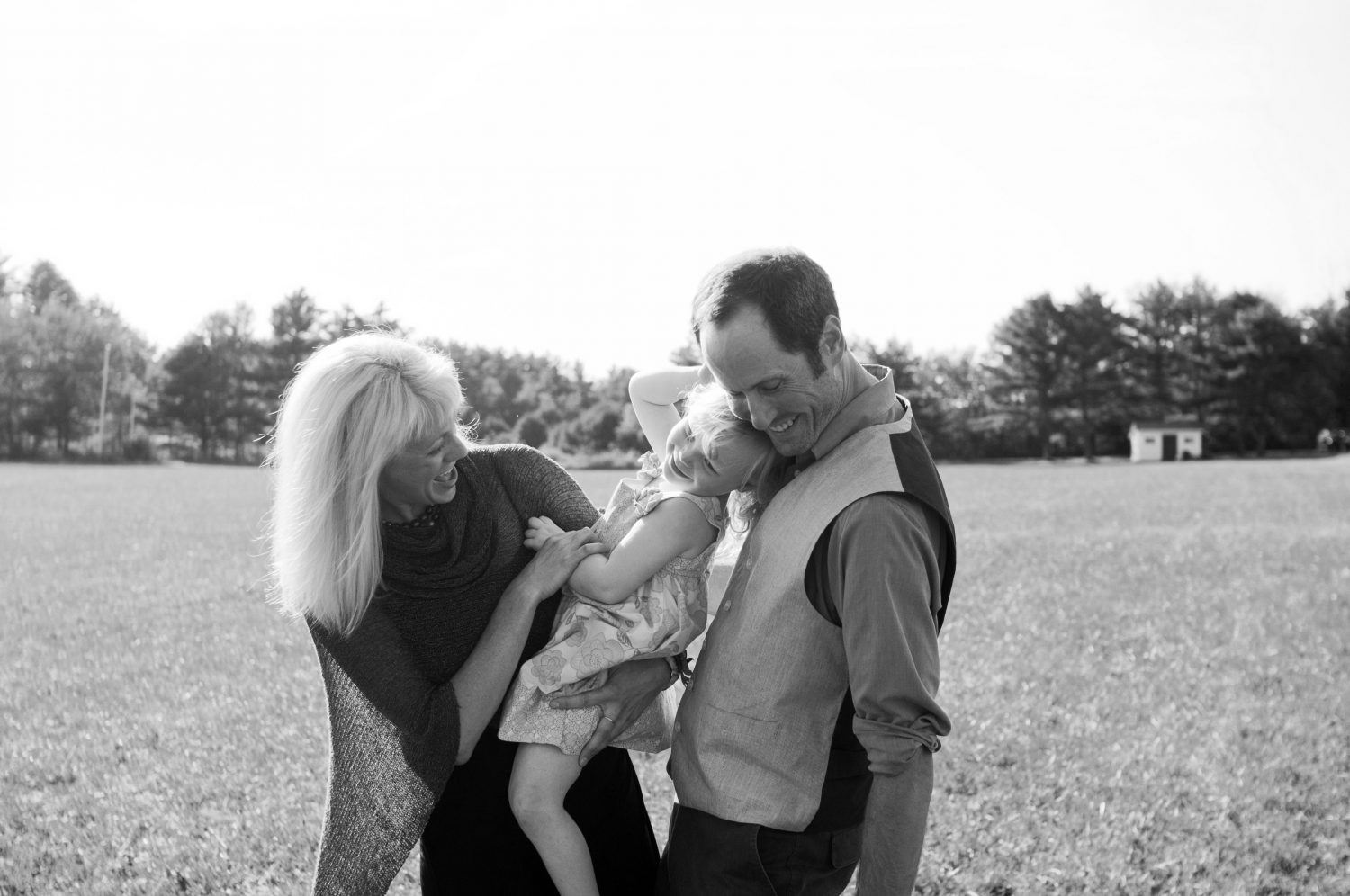 black and white photo of young girl being held by father with mother beside them giggling