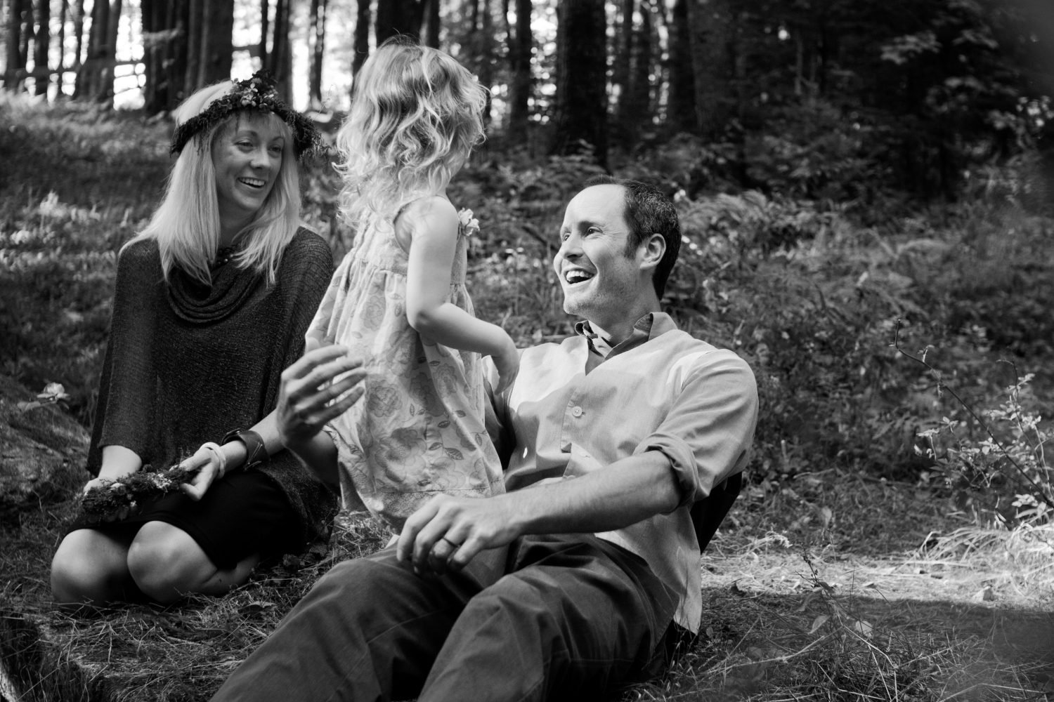 black and white image of young family of three playing together in the forest