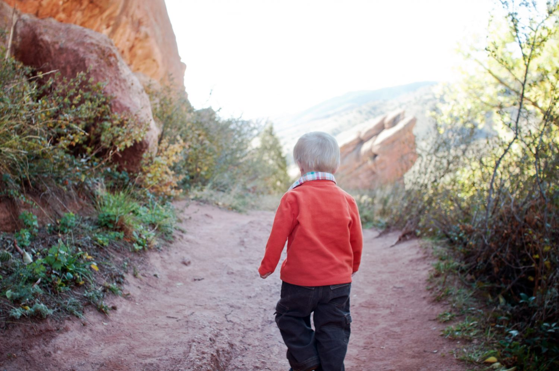 Toddler walking on trail in red rocks, colorado