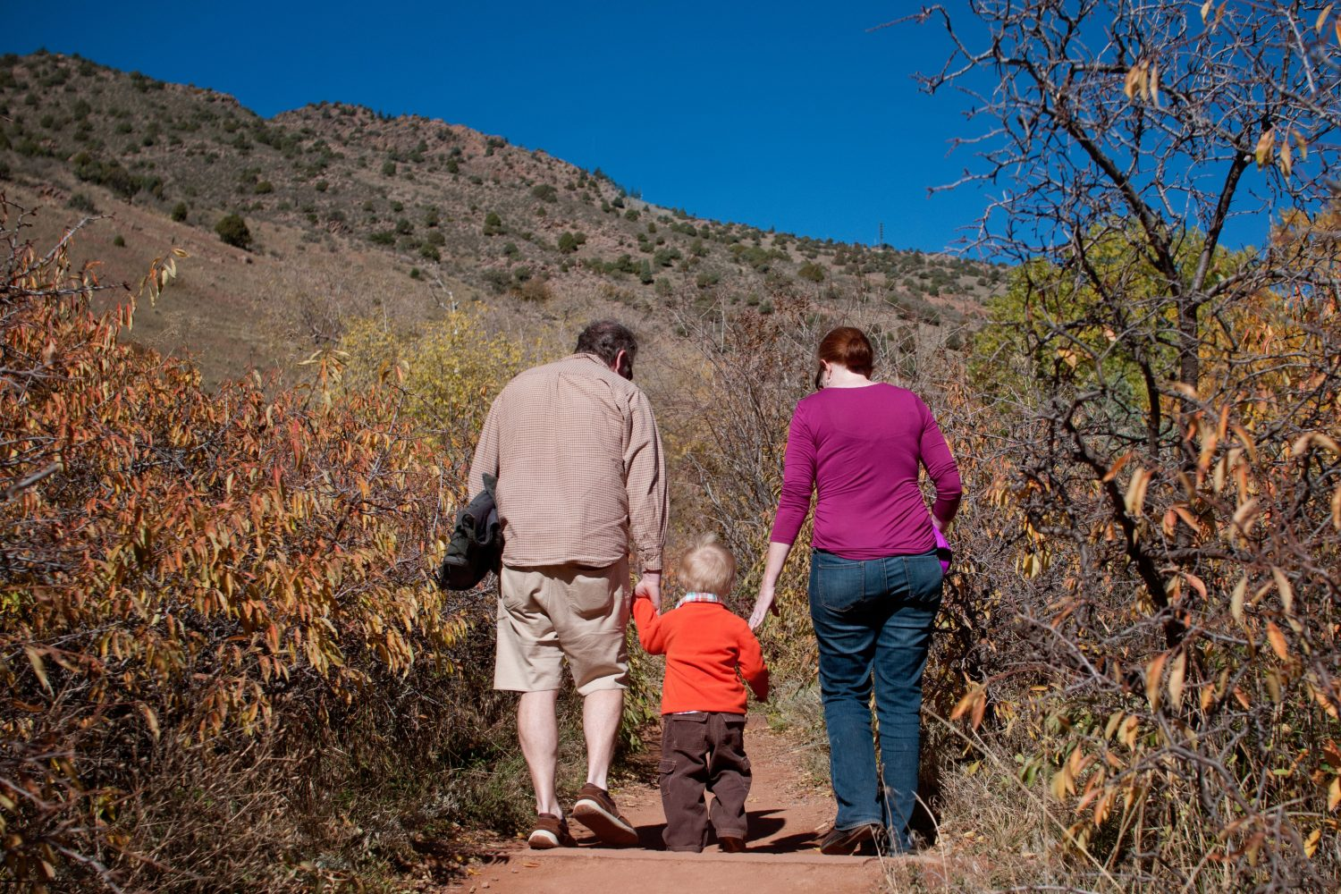parents holding their sons hands as they walk together on a trail at red rocks park