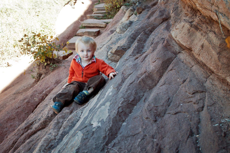 casual portrait of toddler boy sitting on rocks