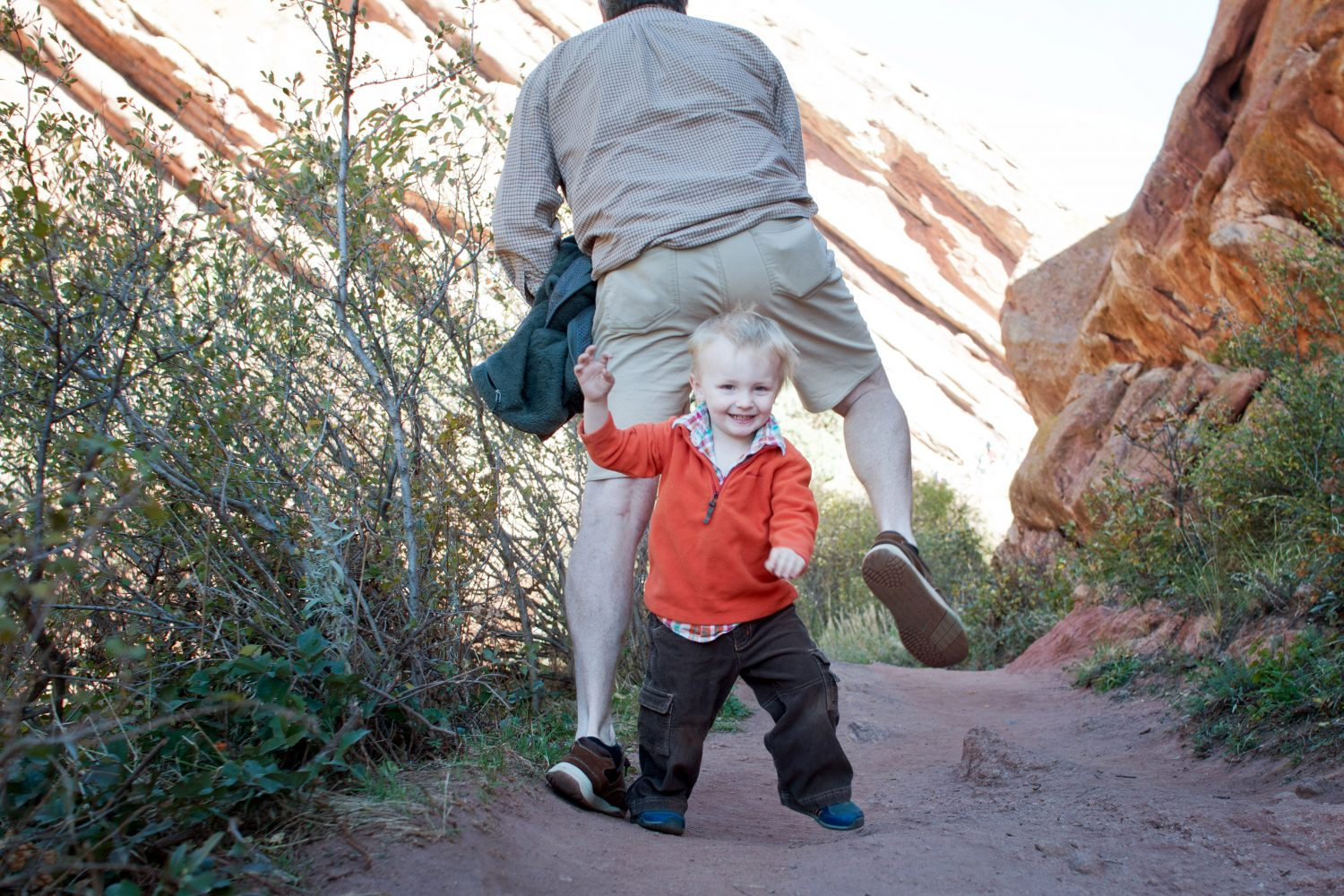 toddler boy running under fathers legs on a trail in red rocks colorado