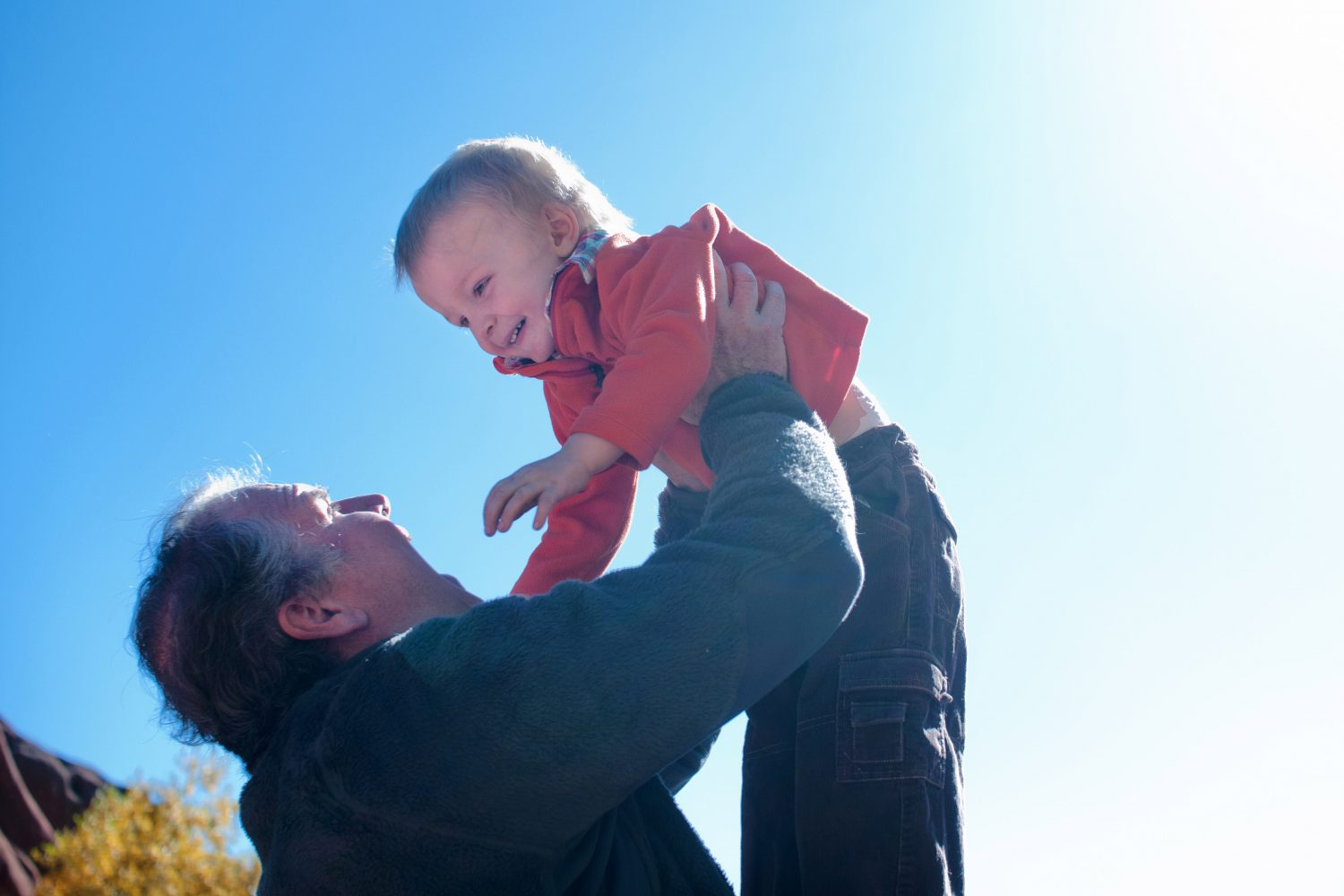 father holding his toddler son up in the air