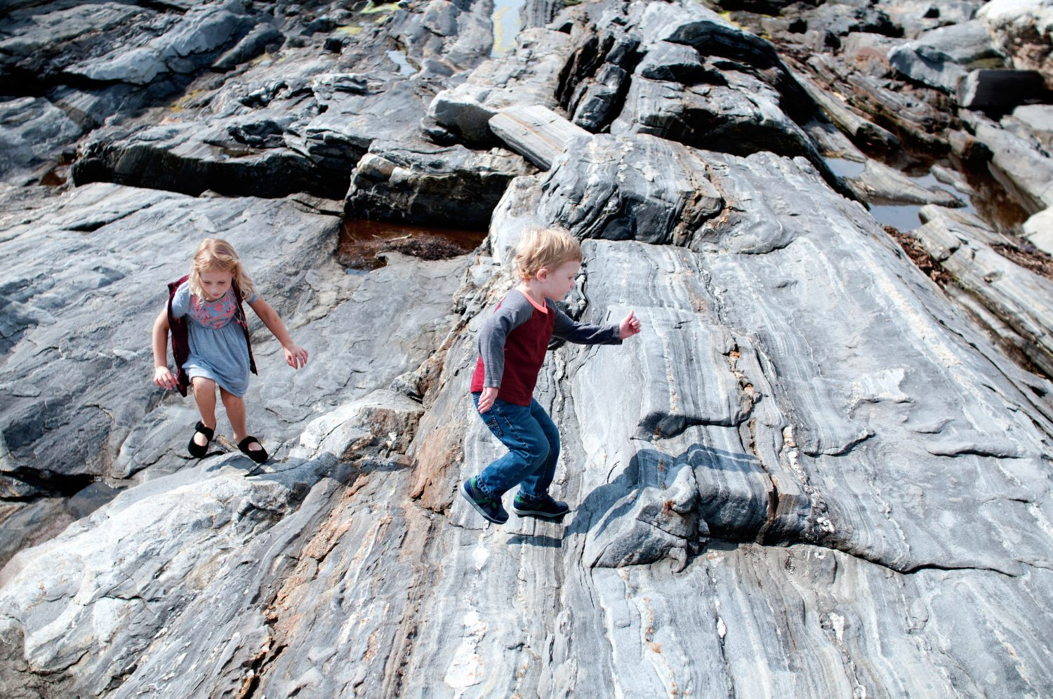 brother and sister playing on rocks at the ocean