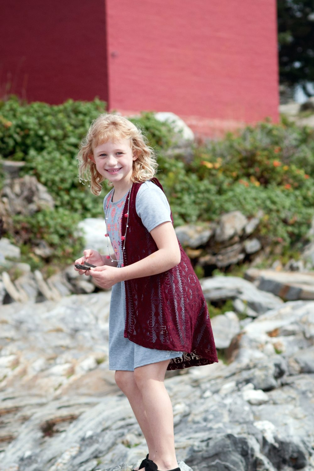 young girl smiling at camera while standing on rocks at Pemaquid Point