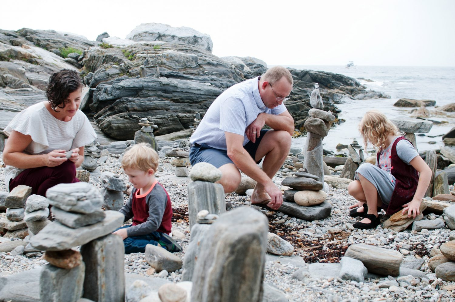 family of four building rock structures on the beach
