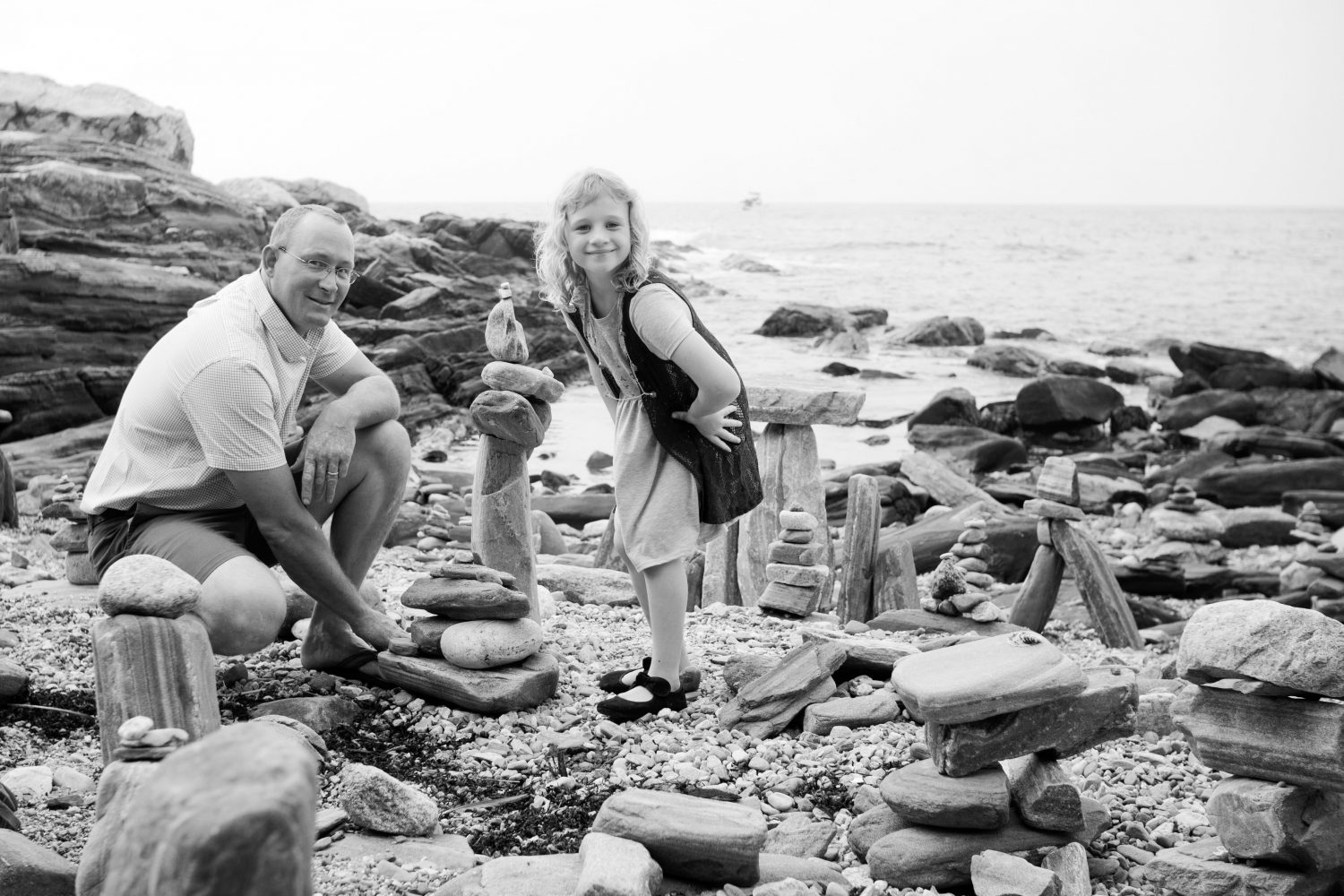 black and white photo of young girl with father building rock formations on the beach
