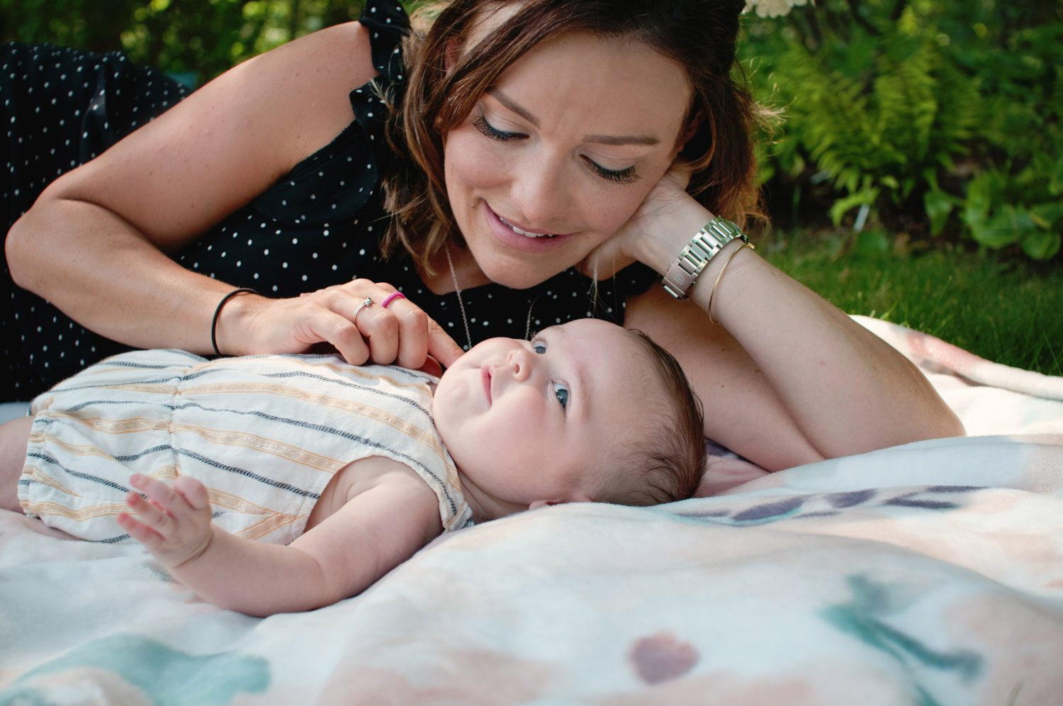 baby laying on blanket in grass with mother beside her smiling