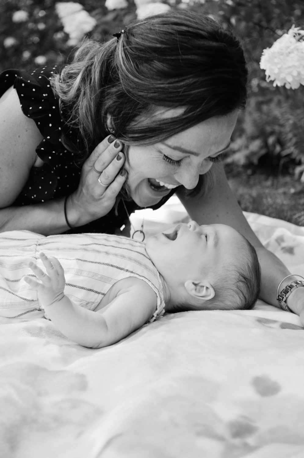 black and white photo of mother playing with her baby daughter