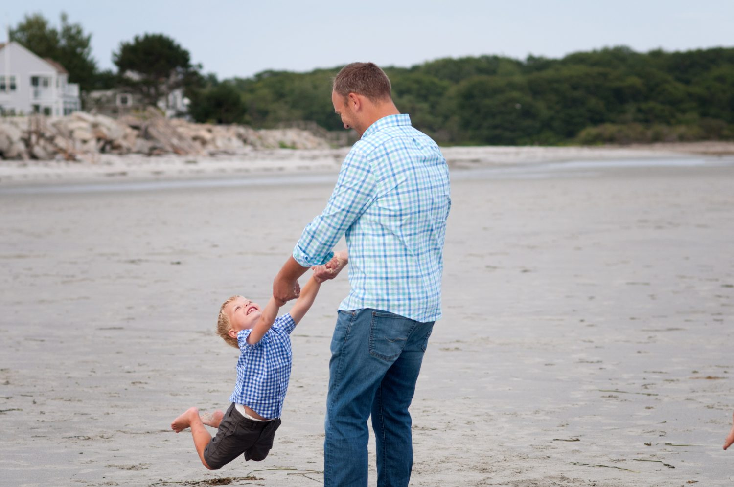 father swinging toddler son in circles at the beach
