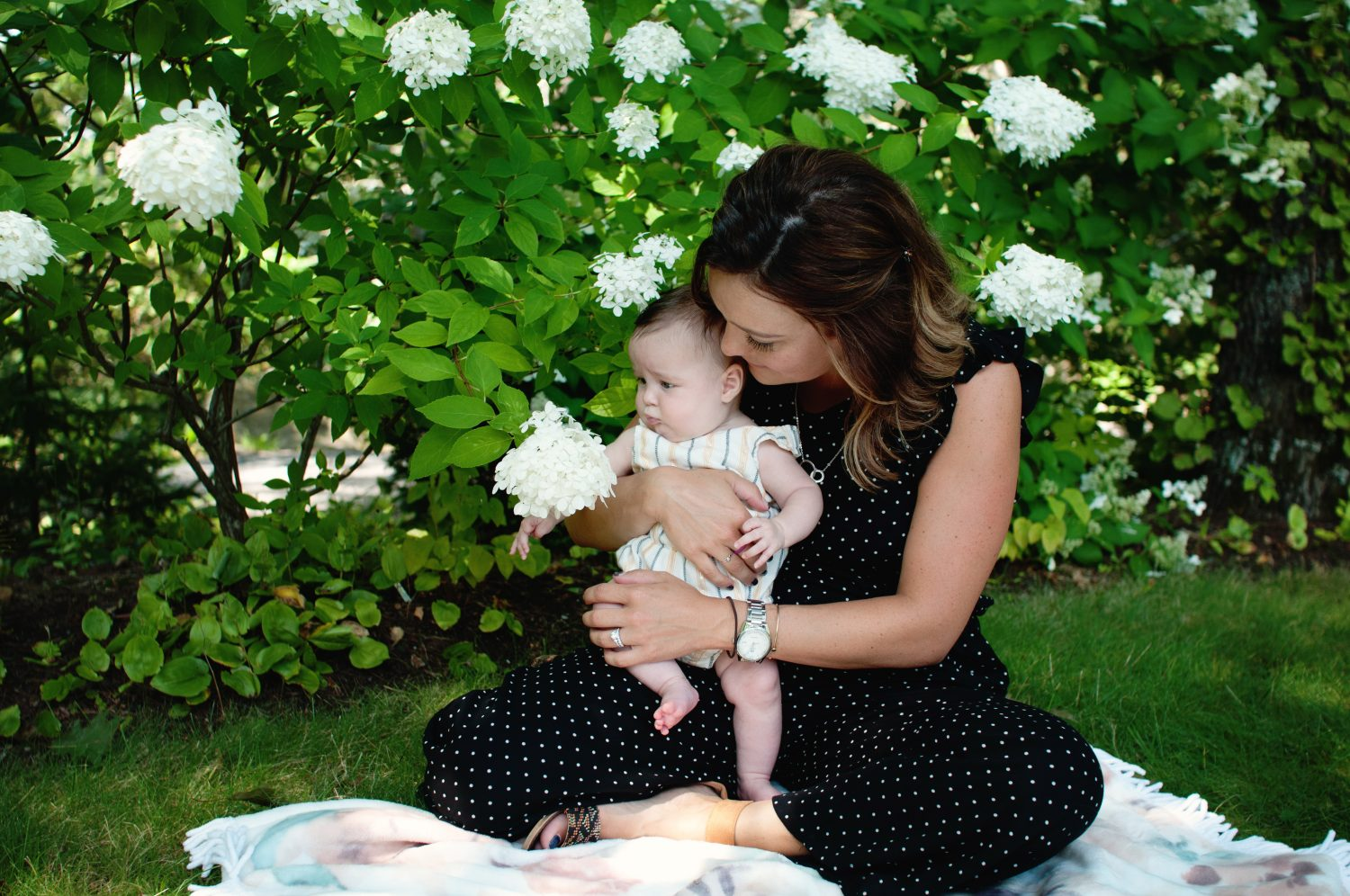 mother holding baby daughter while sitting in grass looking at HYDRANGEAS