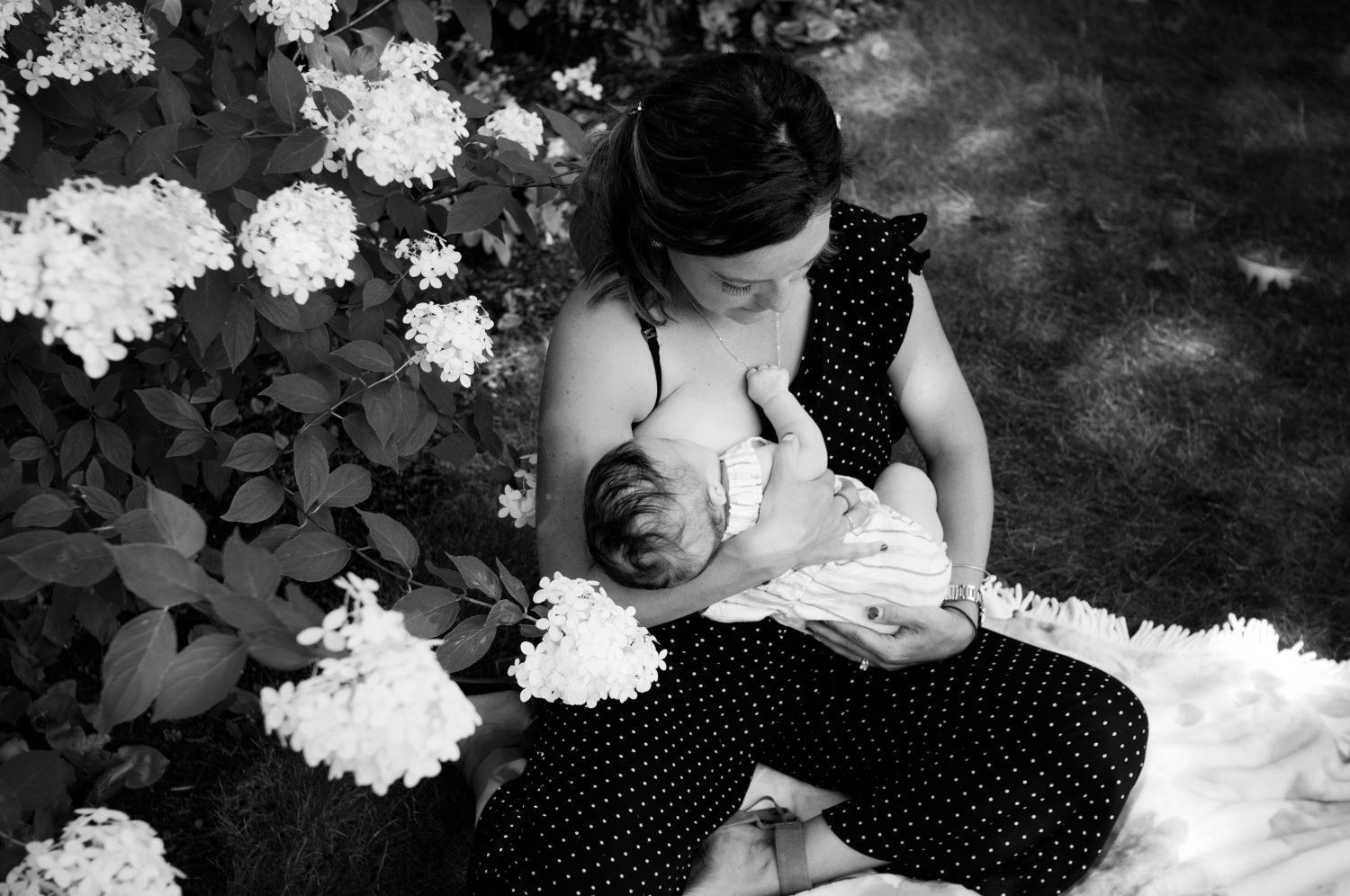 black and white photo of mother breast feeding her baby