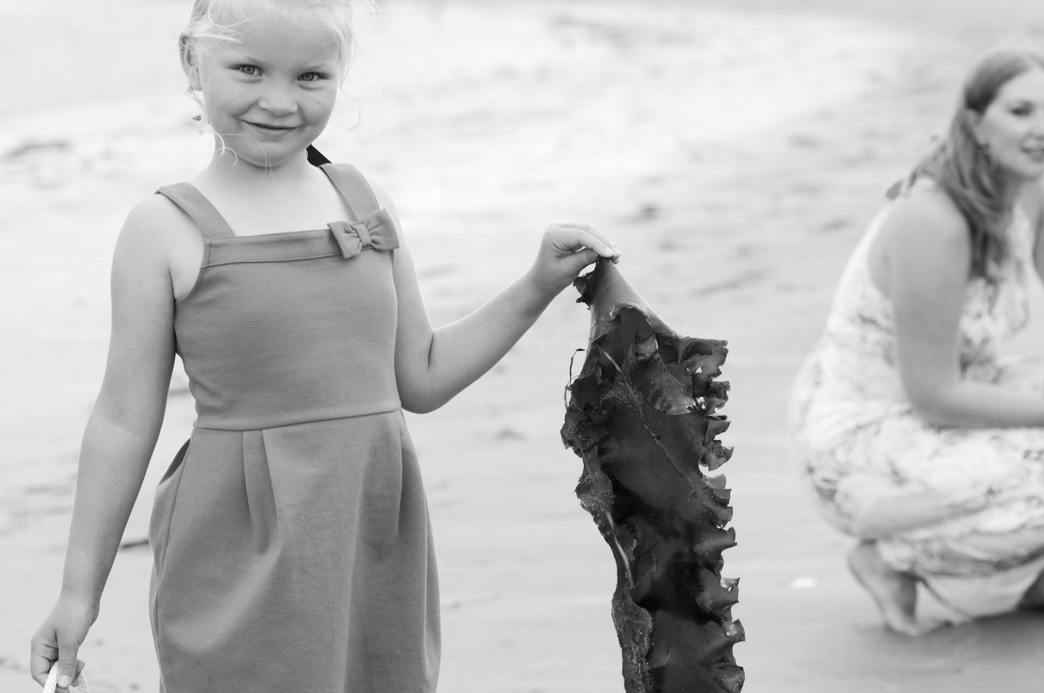 black and white image of little girl holding a large piece of seaweed at the beach