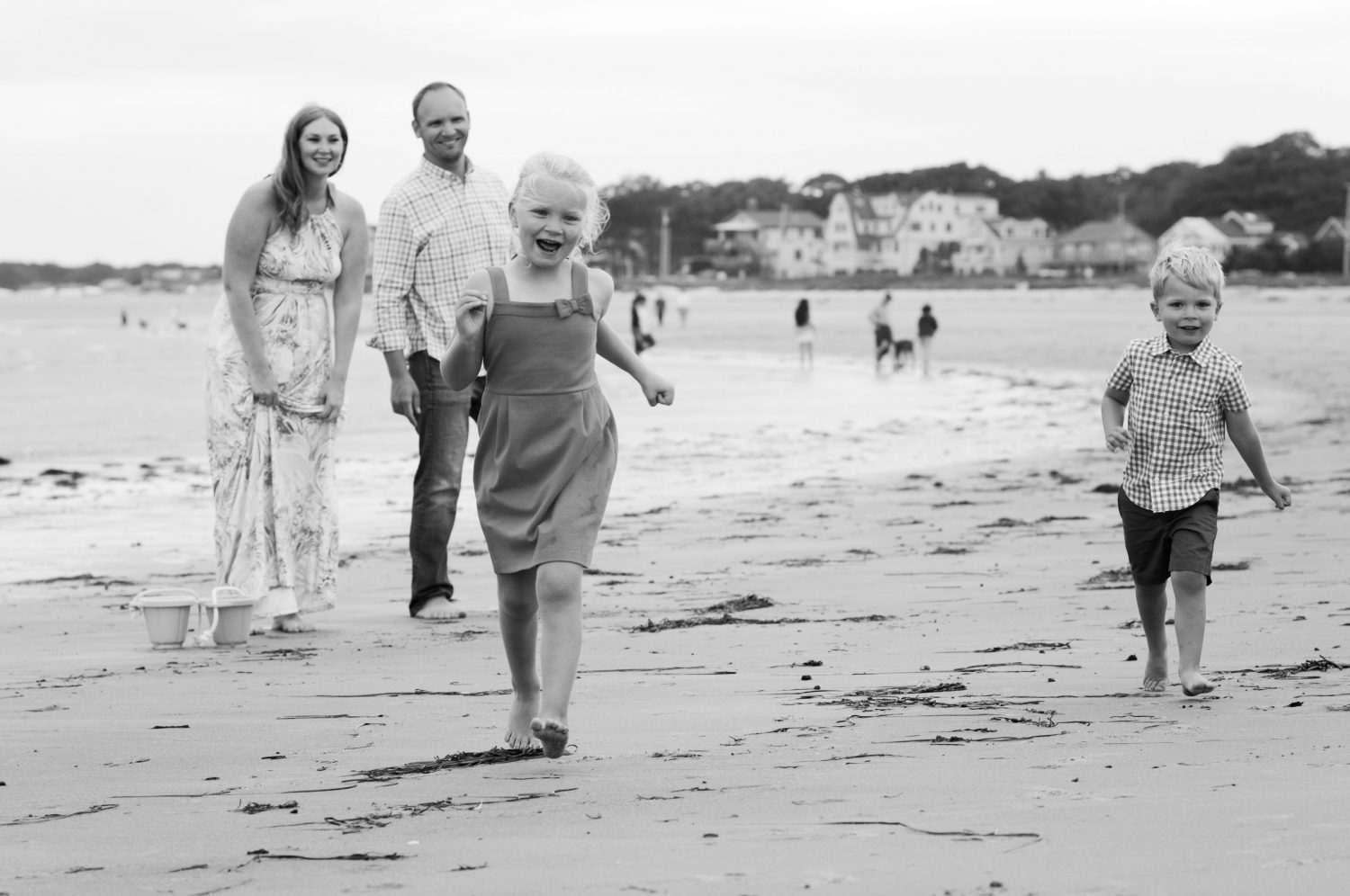 black and white image of young children running on the beach while parents watch