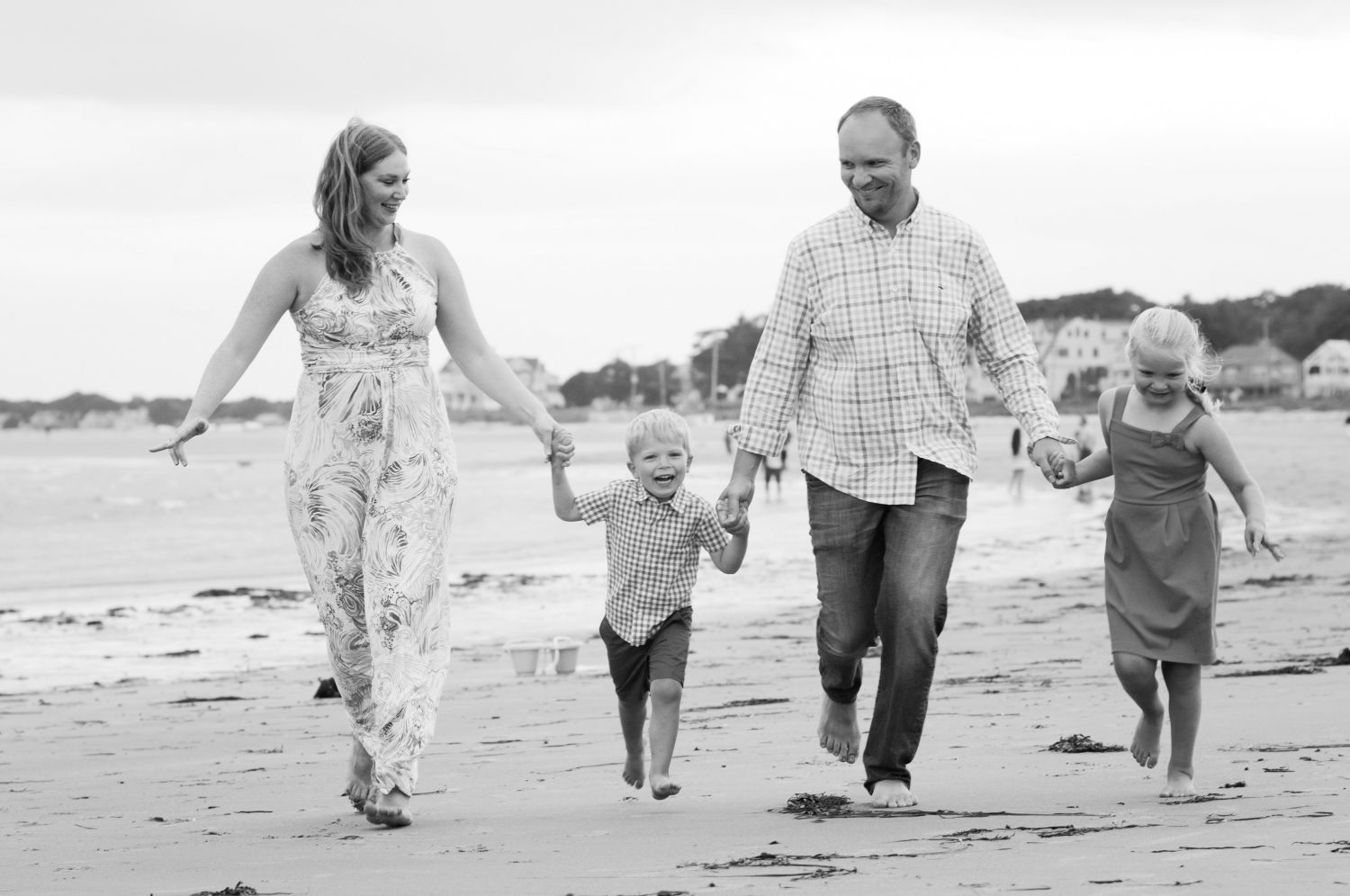 black and white photo of family of four holding hands, laughing and running along the beach