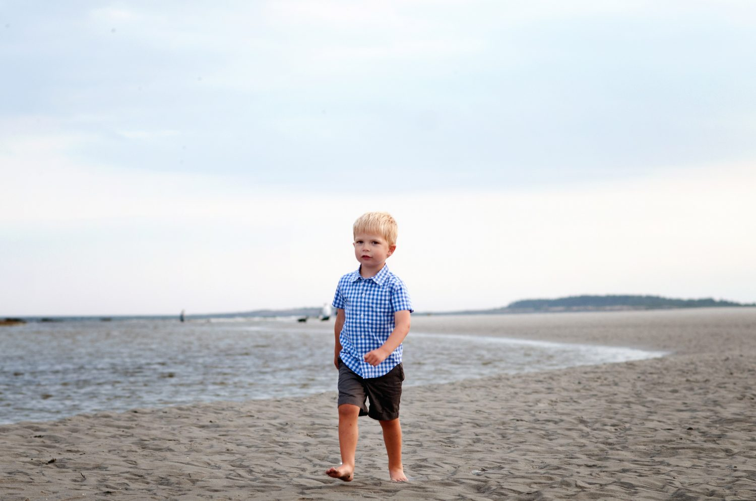 toddler boy walking along the sandy beach at the ocean