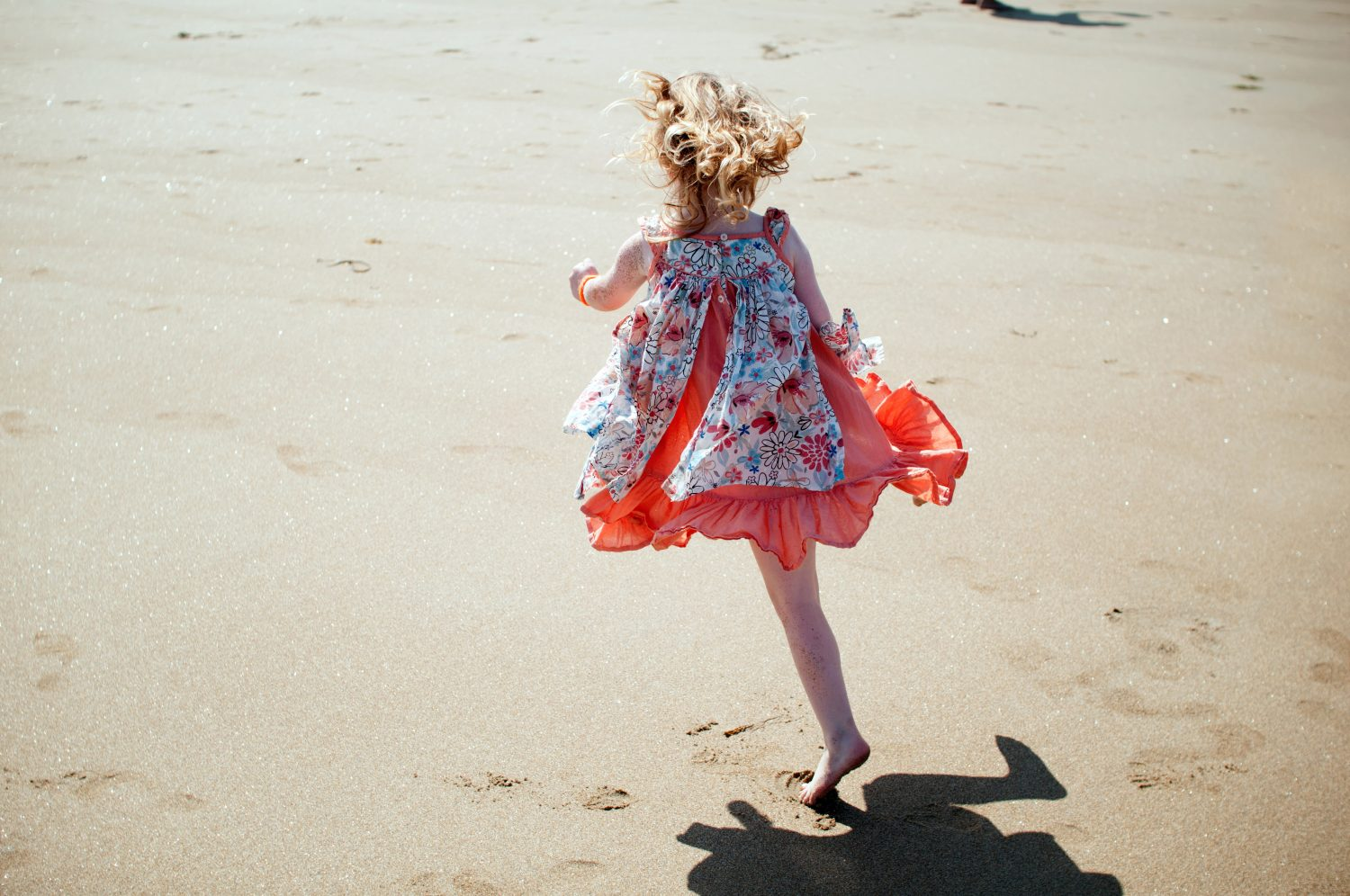 little girl skipping on the beach