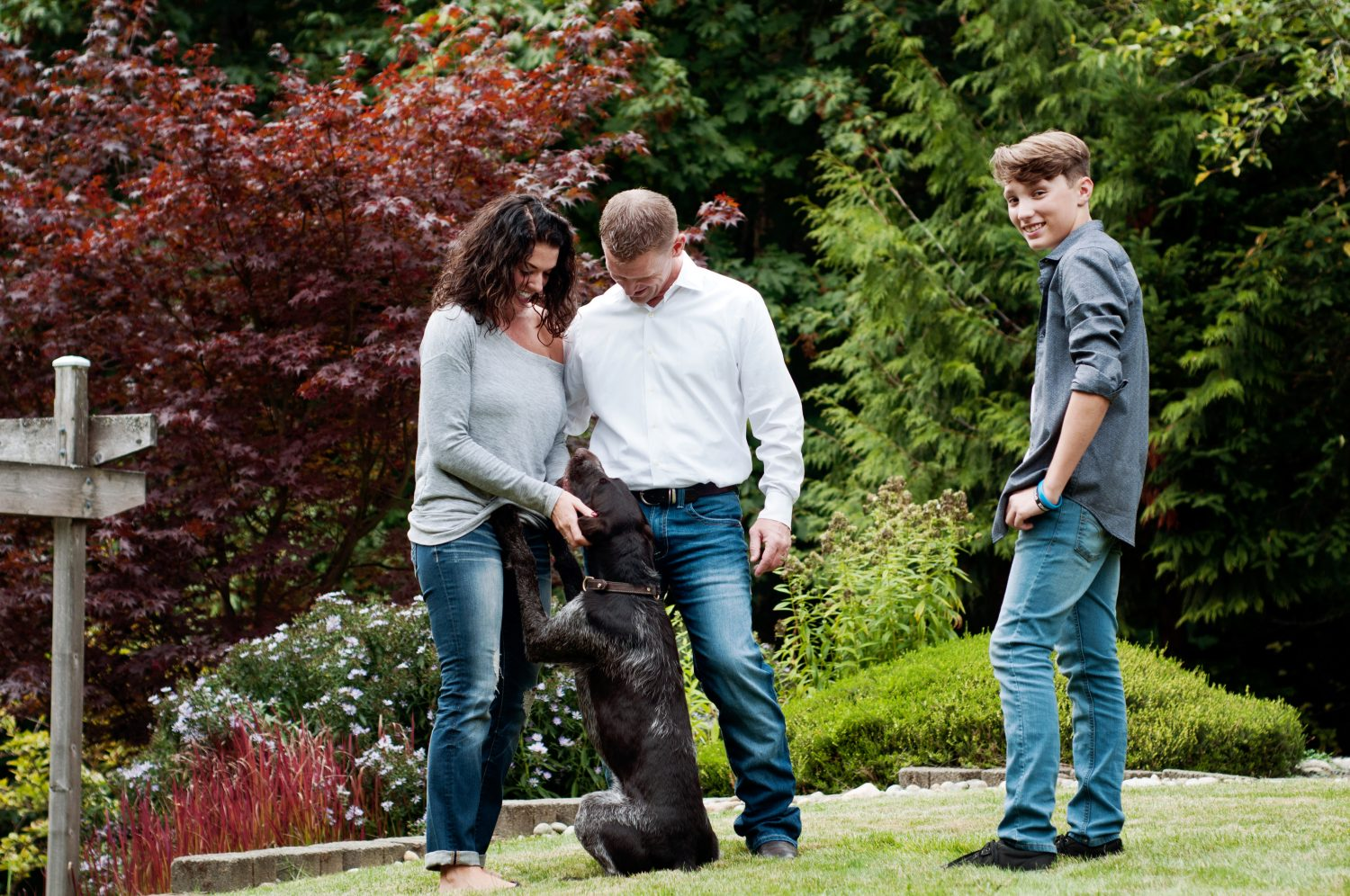 mother, father and teen son with their dog