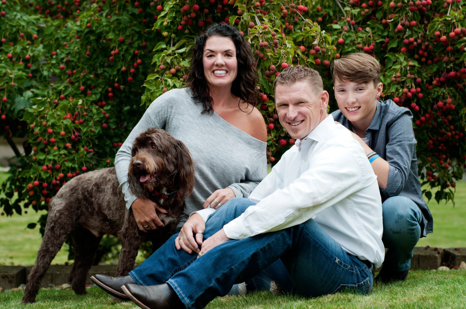casual portrait of mother, father and teen son with dog on the lawn