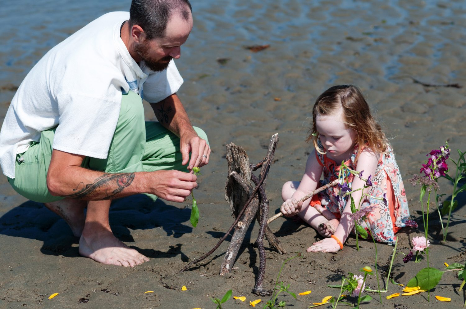 father and daughter playing with sticks and flowers on beach