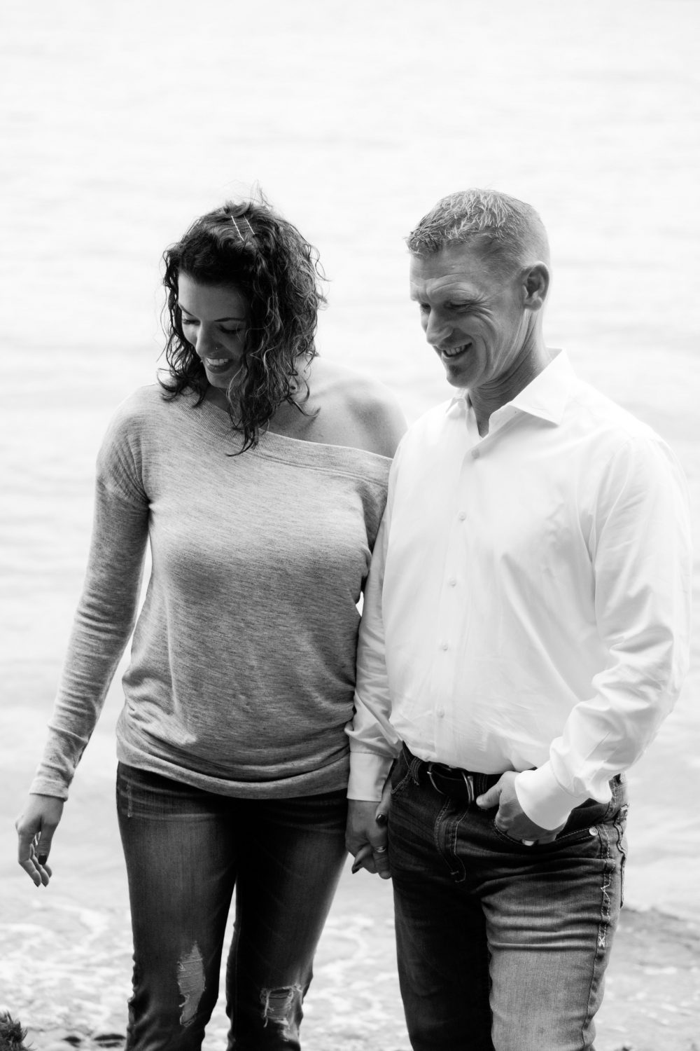 black and white image of husband and wife holding hands smiling