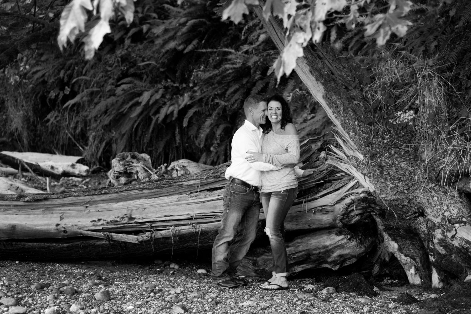 black and white photograph of couple hugging and laughing beneath a tree on the beach