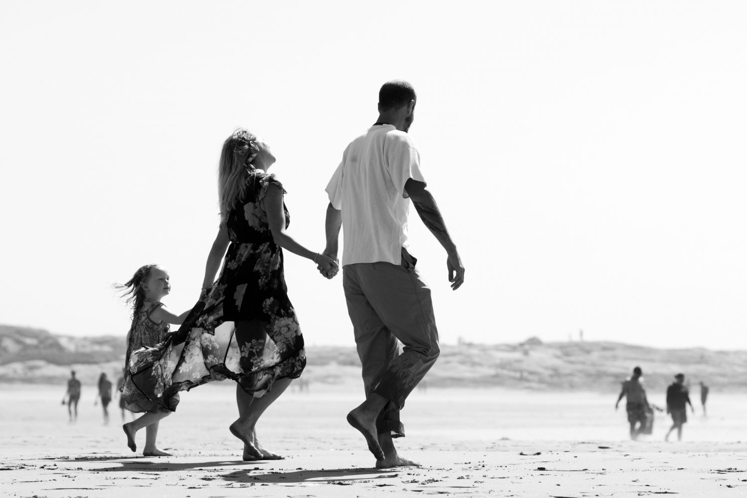 black and white photo of family of three walking along the beach holding hands