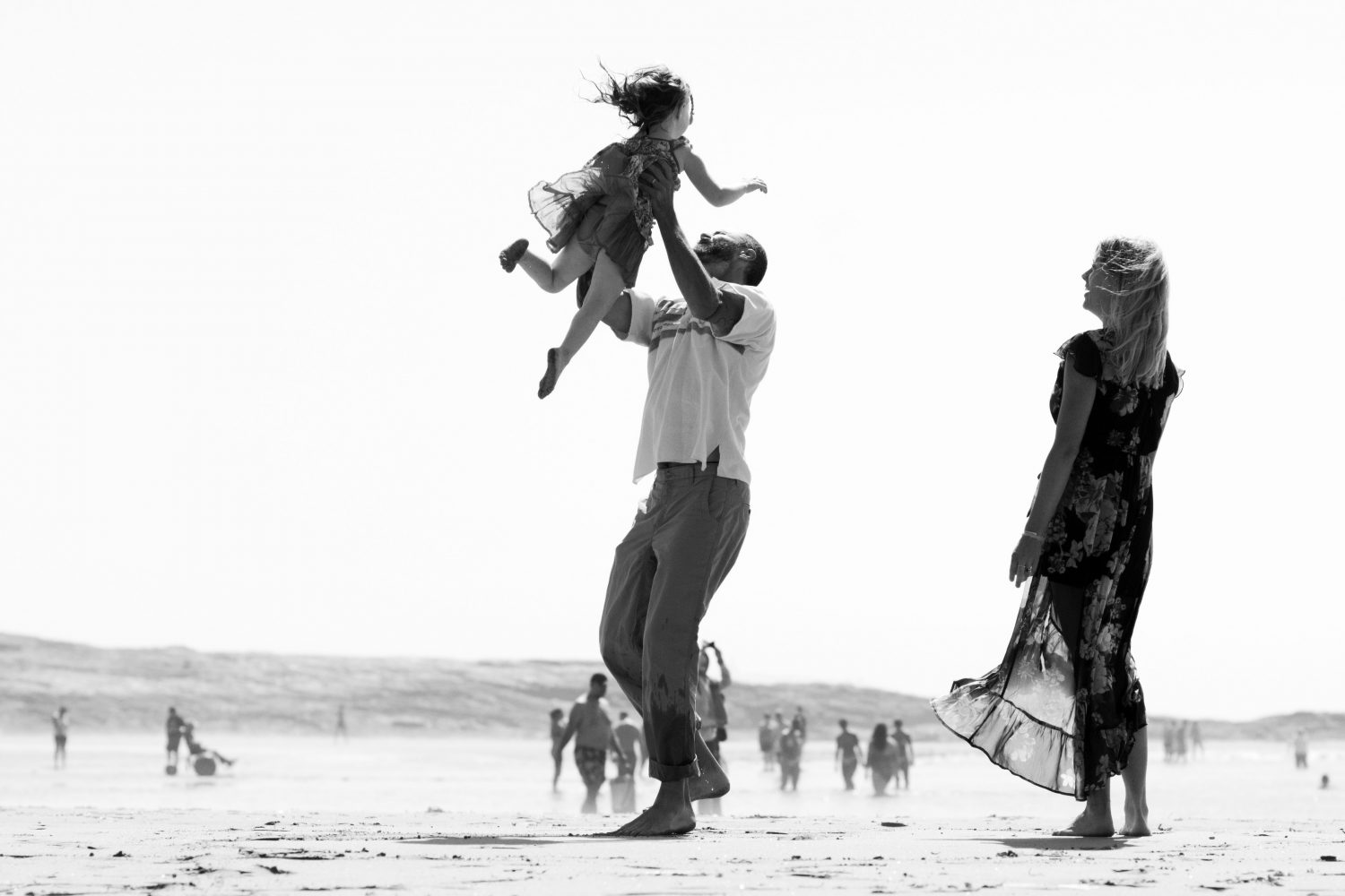 father tossing daughter playfully into the air at the beach