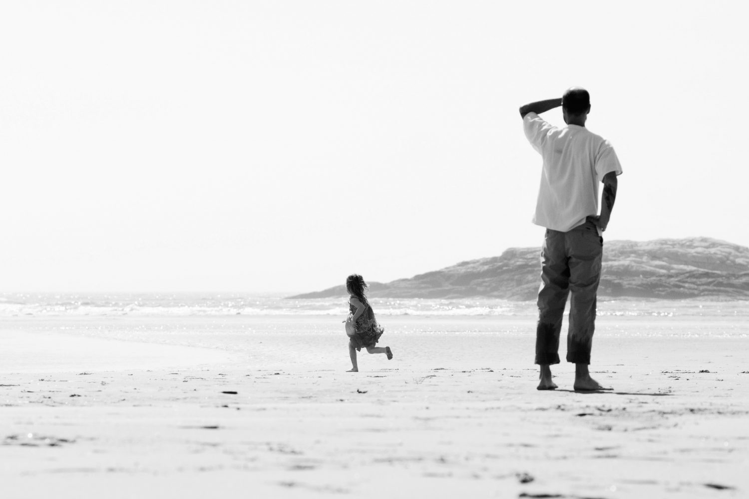 black and white image of little girl running on beach while father watches