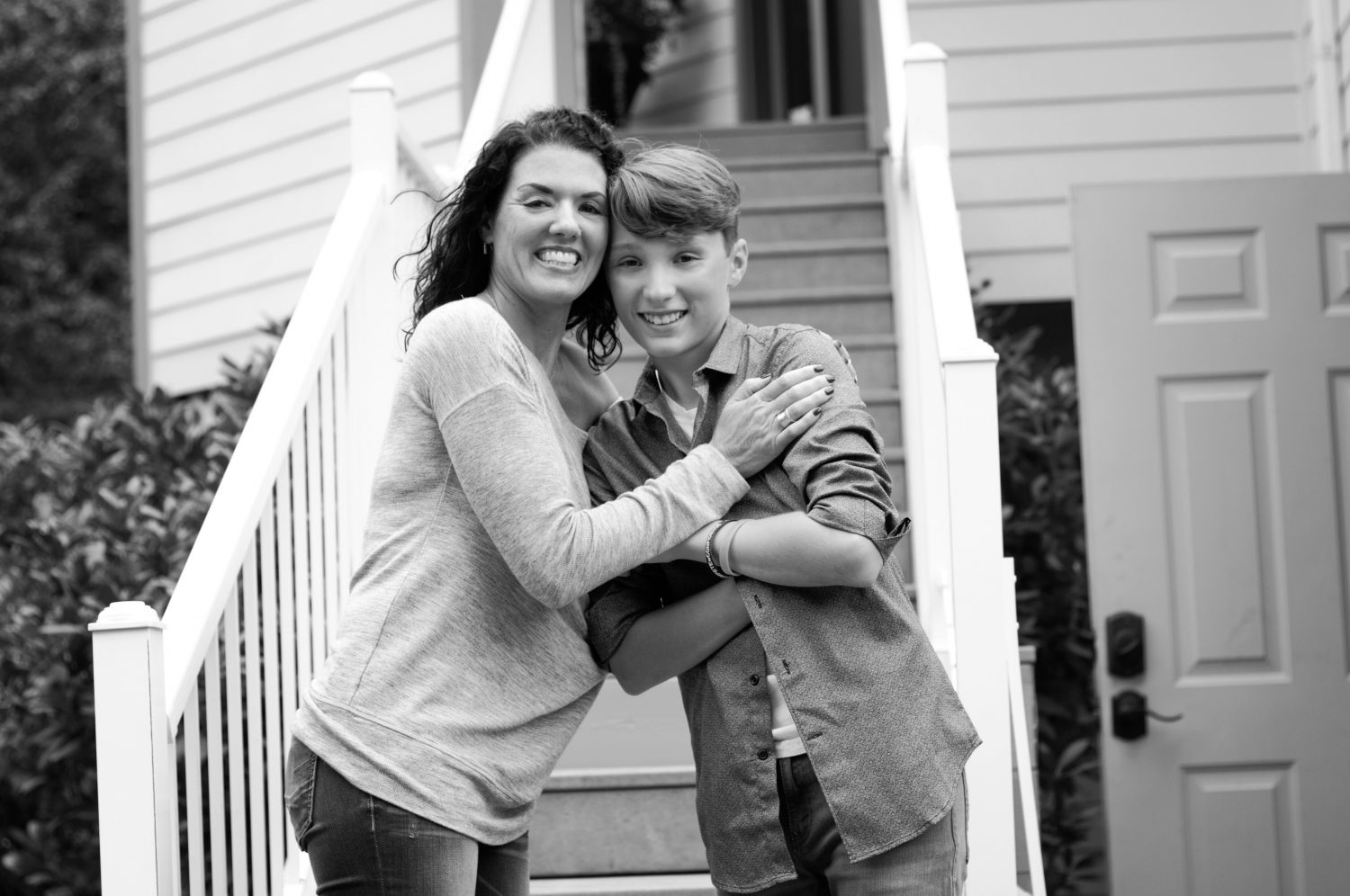black and white photo of mother hugging her teenage son, both smiling