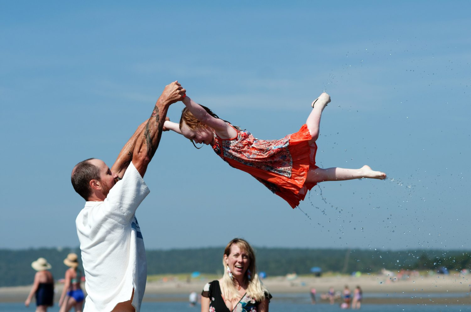 father swinging his daughter into the air at the ocean